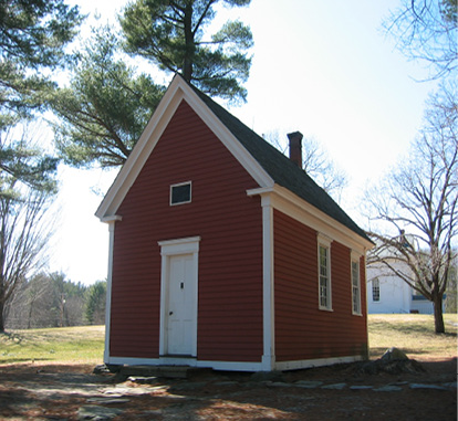 A very small likely 1 room school house with red panneling.