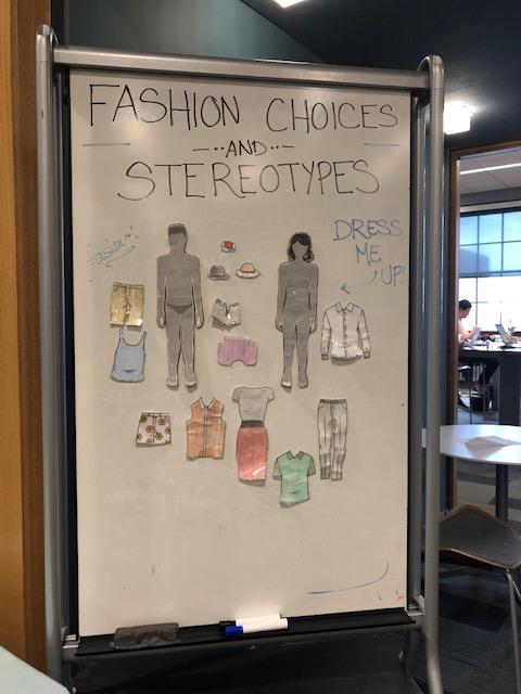 close up of whiteboard: fashion choices and stereotypes, with an invitation to add clothes to male and female figures