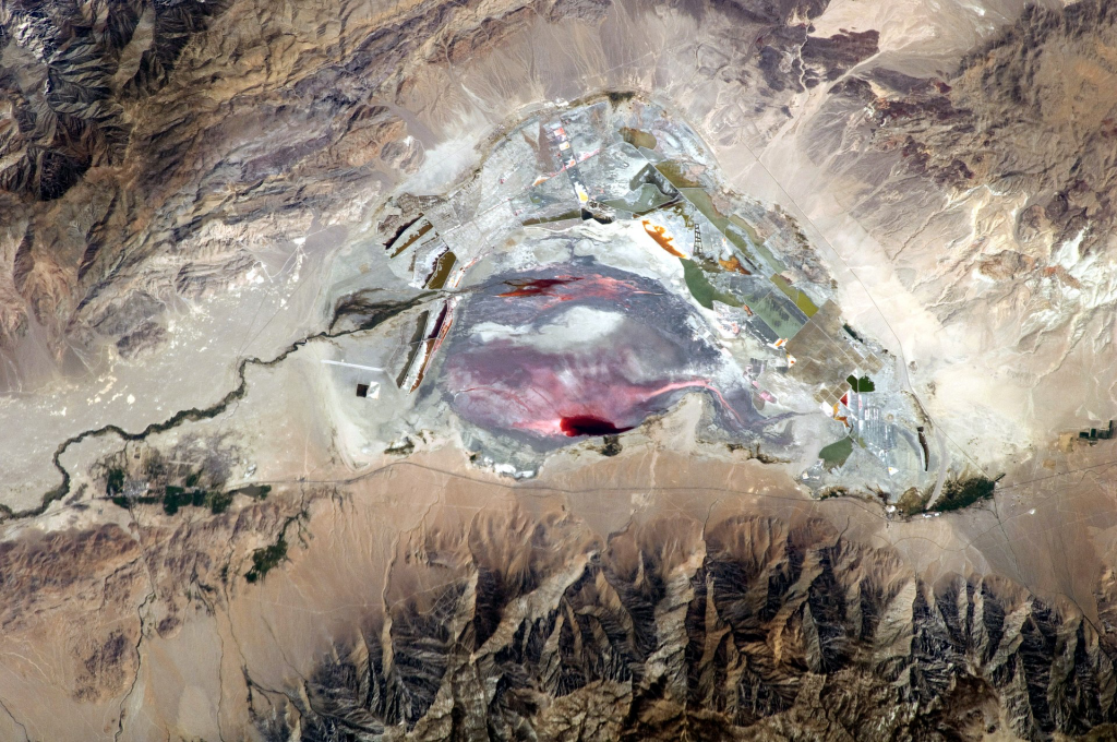 This astronaut photograph highlights the mostly dry bed of Owens Lake, located in the Owens River Valley between the Inyo Mountains and the Sierra Nevada. Shallow groundwater, springs, and seeps support minor wetlands and a central brine pool. Two bright red areas along the margins of the brine pool indicate the presence of halophilic (salt-loving) organisms known as archaeans. Gray and white materials within the lake bed are exposed sediments and salt crusts. The nearby towns of Olancha and Lone Pine are marked by the presence of green vegetation, indicating a more constant availability of water.
