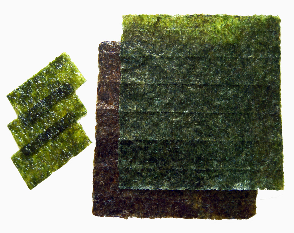 Nori, roasted sheets of seaweed used in Japanese cuisine for sushi. Smaller pieces are also pictured, already seasoned with sesame oil and spices.
